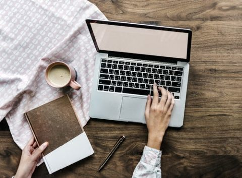 Persoon die op een laptop typt en een boek vasthoudt