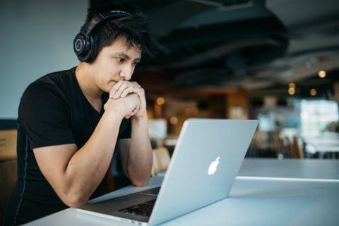 Man die in een café met een laptop zit te studeren